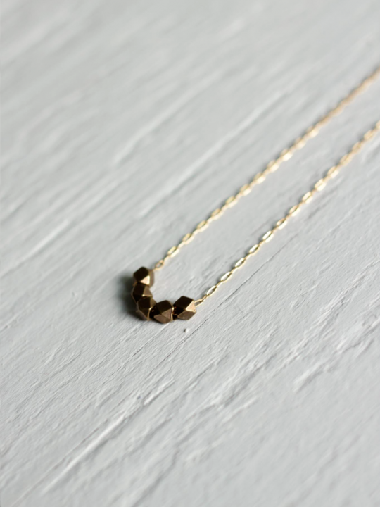 brass bead on gold necklace