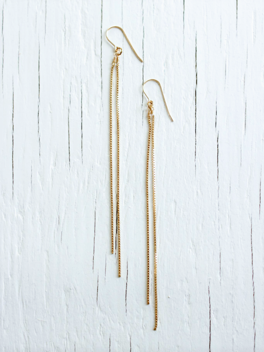 Two earrings made with 2 long gold chains each strung from a gold earwire sit on top of a white wood background