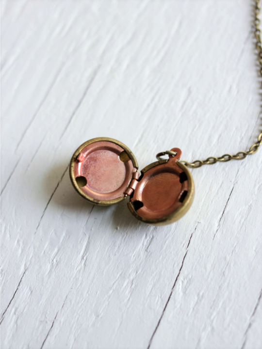 Vintage ball locket strung on a brass chain laying on top of a wood board background