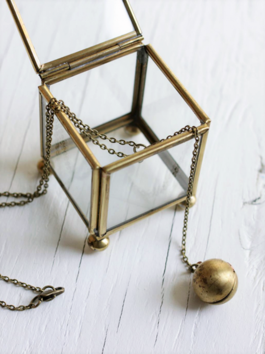 Vintage ball locket strung on a brass chain laying on top of a wood board background laid across a glass treasure box