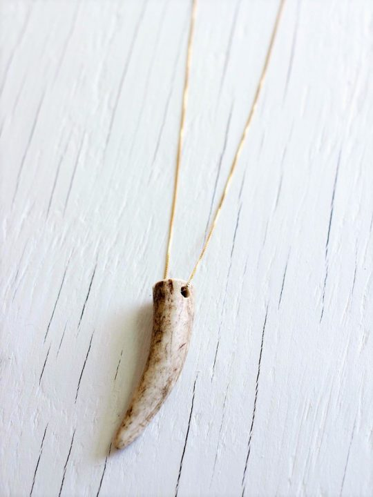 Deer antler necklace strung on a 14kt gold fill chain laying on top of a white wood backgrund