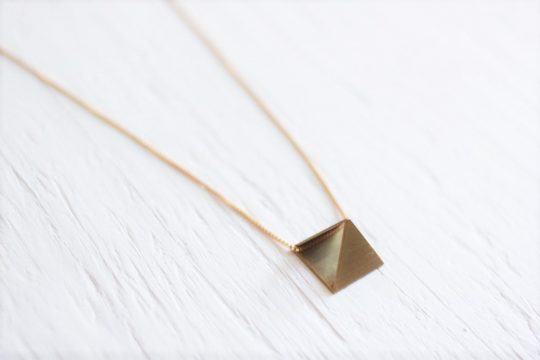 Gold pyramid necklace with raw brass pyramid pendant strung on 14kt gold fill chain laying on white wooden background