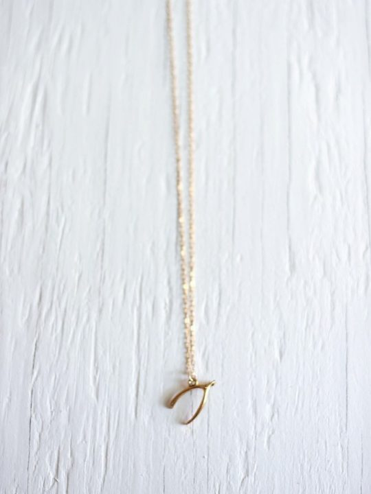 gold wishbone necklace on a gold chain