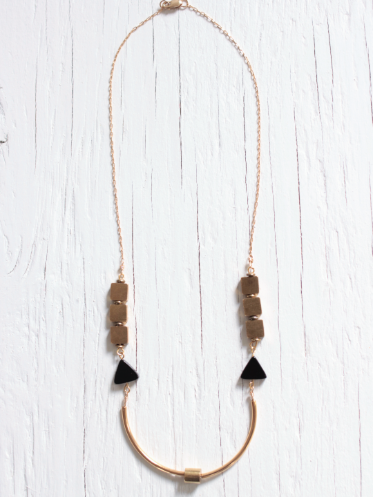 Art deco necklace featuring curved brass bars around a brass tube bead, black onyx triangle beads and brass cube beads strung on a 14kt gold fill chain laying on top of a white wood background