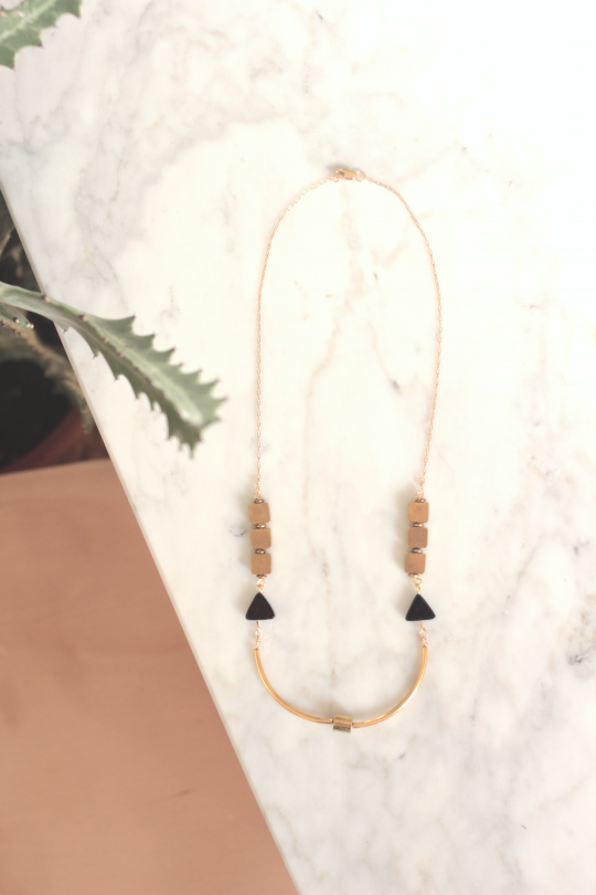 Brass bar necklace has curved bars and two black onyx triangles
