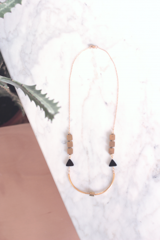 Art deco necklace featuring curved brass bars around a brass tube bead, black onyx triangle beads and brass cube beads strung on a 14kt gold fill chain laying on top of a white marble table next to a cactus plant
