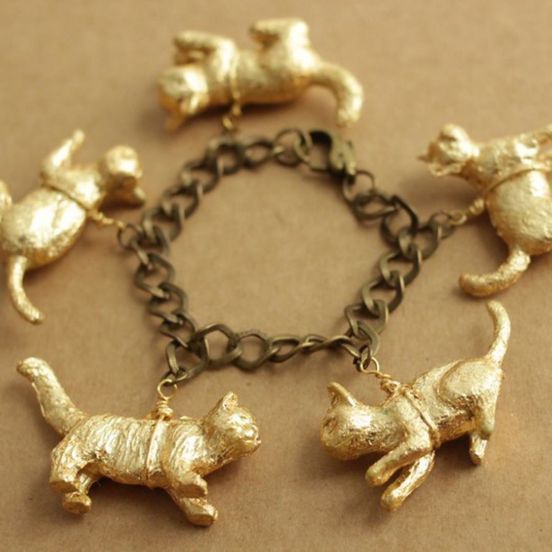 This image is a cat charm bracelet made with gold leaf covered plastic cat charms.