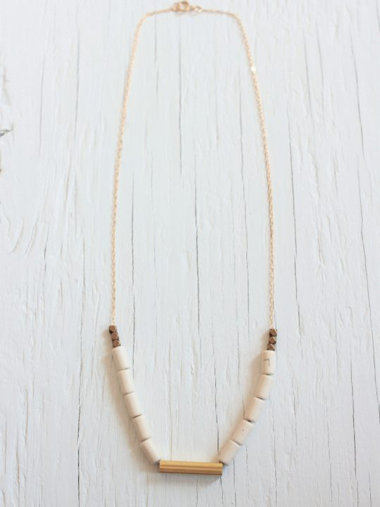 Delicate beaded necklace with brass bar on a white wood background