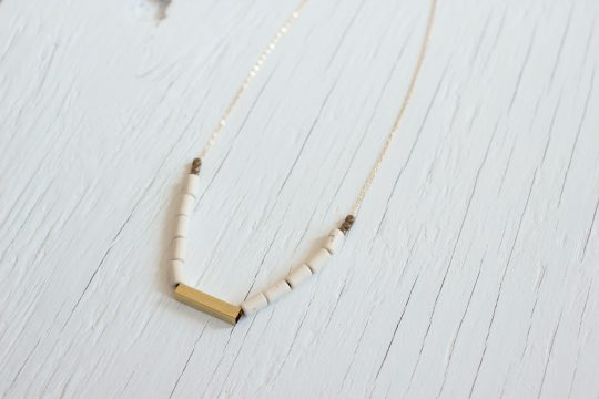 Beaded necklace with white tube beads and a brass tube on a gold chain, laying on a white wood background