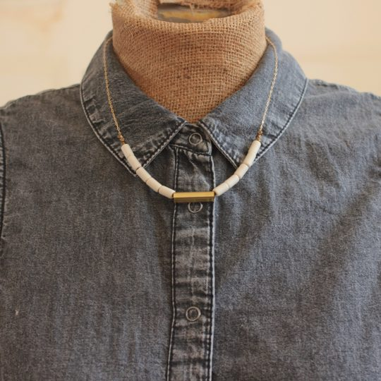 Minimalist white bead and gold necklace on a mannequin wearing a gray button down shirt