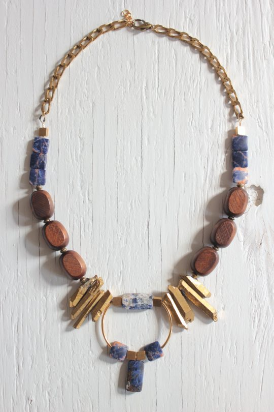 Bib necklace features blue sodalite stones, wooden beads, gold dipped prisms and geometric brass components