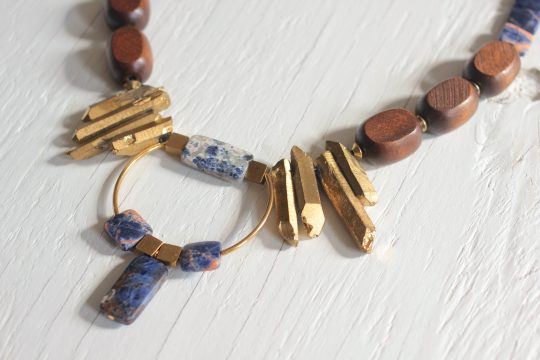 Bib necklace features a circular pendant made with brass tube and blue sodalite stones