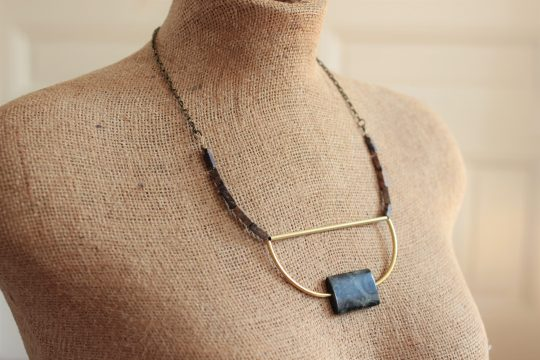 Modern necklace with a green jasper focal stone, curved brass bars, rectangle stones on a brass chain on a mannequin in front of a beige wall