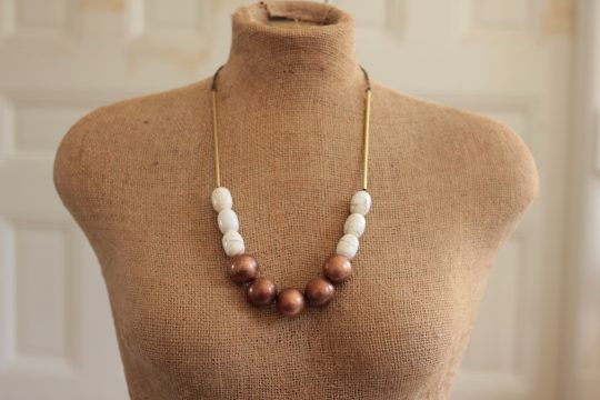 Mannequin wearing a copper ball necklace in front of a white wall