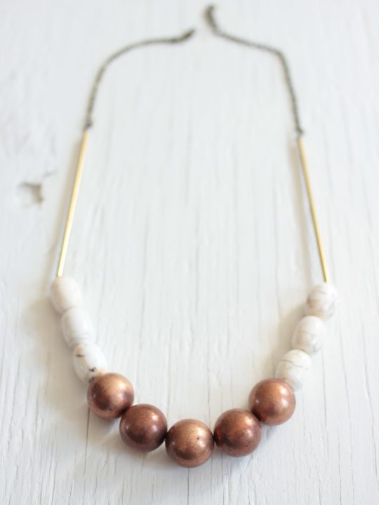 Statement necklace made with copper balls, white magnesite stone barrels strung on a raw brass chain laying on a white wood table