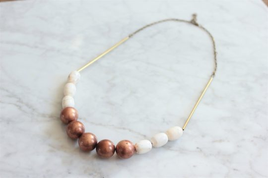 Statement necklace made with copper balls, white magnesite stone barrels strung on a raw brass chain laying on a white marble table