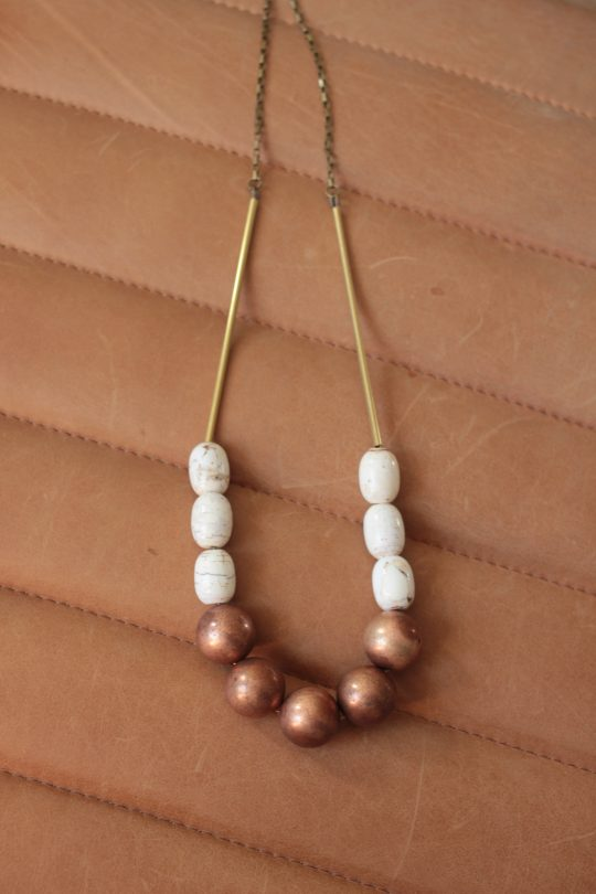 Statement necklace made with copper balls, white magnesite stone barrels strung on a raw brass chain laying on a tan leather background