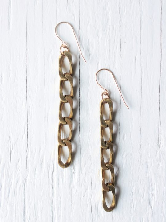 Gold chain earrings on white background