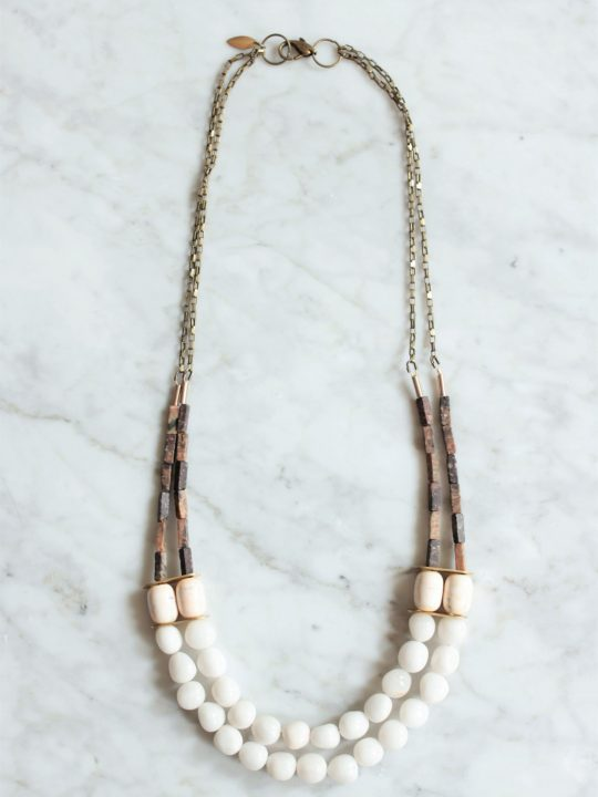 White stone statement necklace with 2 multi strand layers laying on top of white marble table