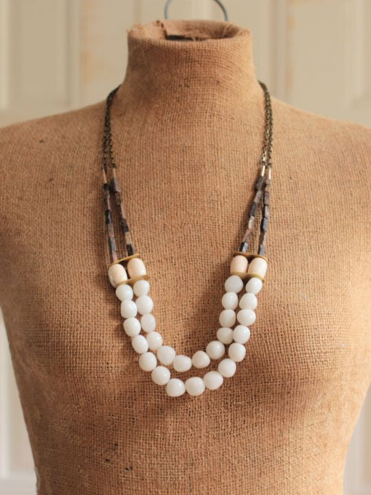 White Bead necklace featuring 2 layers of strands, worn on a mannequin in front of a white background